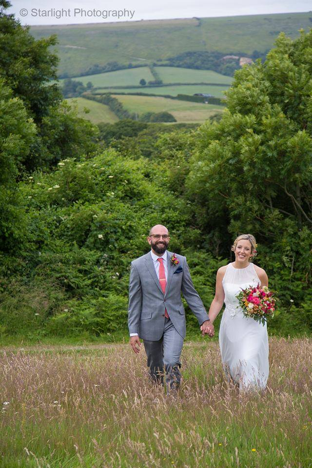 Bride and Groom walking through the fields at Wilkswood Wedding Venue
