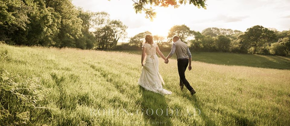 Bride and Groom walking through the fields at Wilkswood